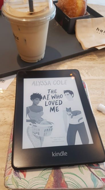 A Kindle e-reader sitting in front of an iced coffee and a donut on a wooden table. The book displayed on the reader is The A.I. Who Loved Me. There is a Black woman, an Asian man, a house cat and a basket of laundry on the cover.