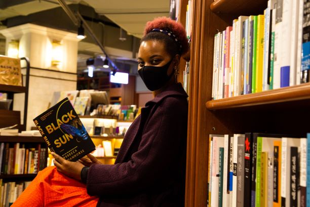 Black woman with afro-puff seated, reading a copy of Black Sun