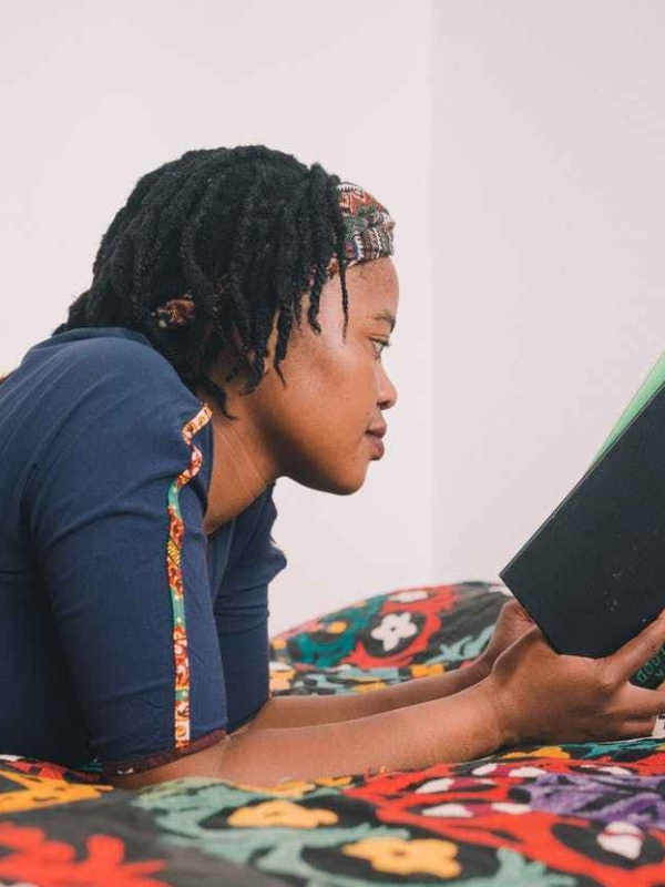 Black woman reading green hardcover book while lying on colorful bedspread