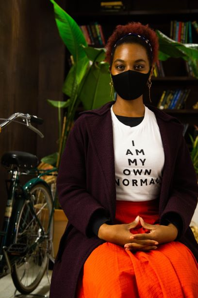 "Black woman with afro-puff seated in front of a bookshelf, wearing red skirt, purple peacoat and white tshirt that says ""I Am My Own Normal"" in black."