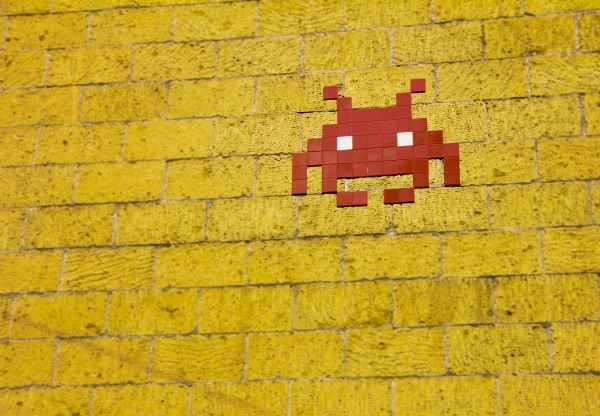 "Yellow brick wall with red mosaic ""Space Invaders""-style alien in top right corner."