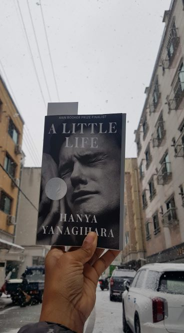 Black and white book with photo of man's tightened face on cover held up in front of apartments buildings on a snowy street