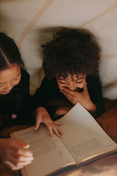 Two children reading underneath a blanket tent. One child is dark-skinned and curly-haired. The other is Asian, with long black hair and a middle part. They are giggling.