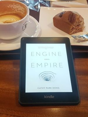 A black Kindle Paperwhite with a white electronic book cover display, lying on a table in front of a wooden tray containing a half-drunk latte and a half-eaten chunk of cake
