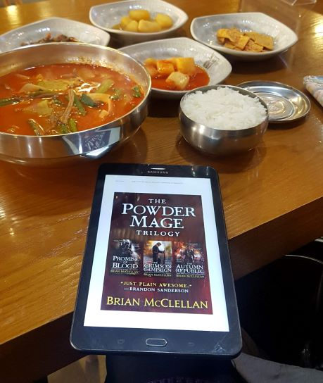A maroon book cover displayed on a black and white hand-held tablet. The tablet rests on a wooden table with a variety of large Korean food dishes--soup, rice, side dishes-- laid out on it.