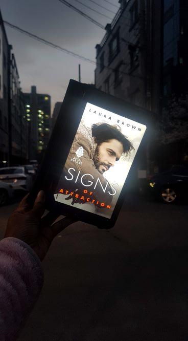 A brightly lit tablet displays a book cover photo of a bearded Latino, held up in front of a narrow dark urban street.