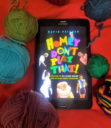 Tablet displaying colorful cover for the book Homey Don't Play That. The tablet is lying on a red blanket, surrounded by multicolored balls of yarn.