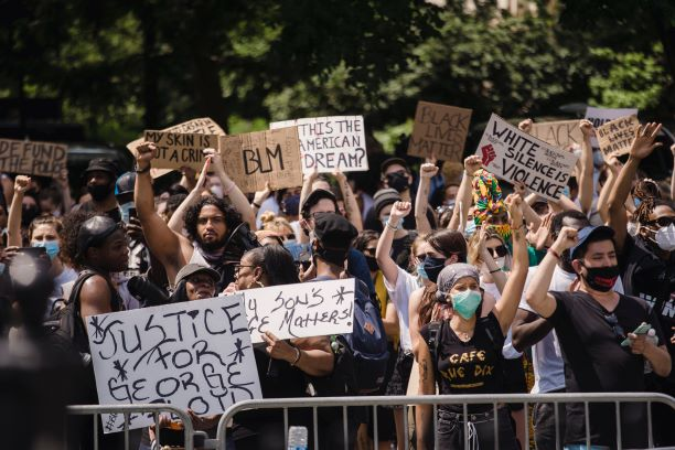 A protest held by many people of different races and genders, behind a waist-high temporary mental fence. Several of the people are holding handmade signs with protest slogans like BLM, Justice for George Floyd, and White Silence Is Violence