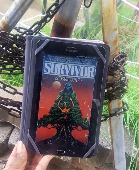 A tablet displaying the cover of Survivor(a woman trapped in a green tree with a furry blue man growing from the top of it, on a red background) held in front of metal stakes chained together standing in the grass