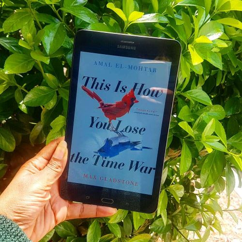 ID: A black tablet displaying the cover of This Is How You Lose The Time War(sky blue background with red and blue cardinal birds reflecting each other surrounded by title text). The tablet is held in front of a leafy green bush by a black woman's hand.