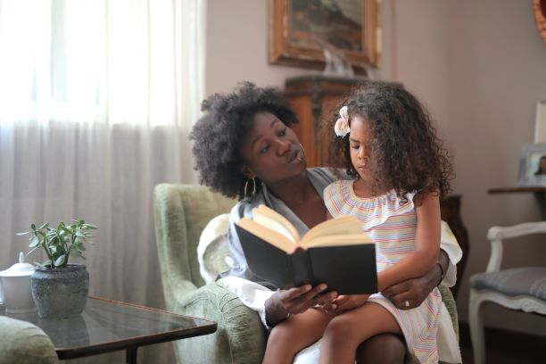 Black mother reading a book to biracial daughter in beautiful house