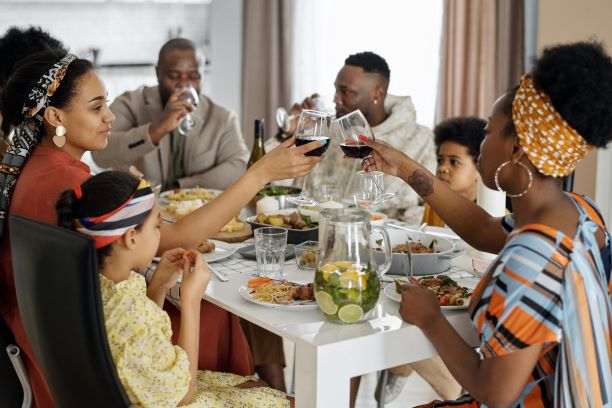 Black family sitting down and having a meal at a table.