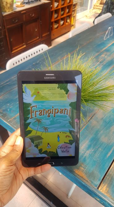 A Black woman's hand holding an ereader displaying the colorful cover of Frangipani in front of a grassy plant and a wooden table painted blue.
