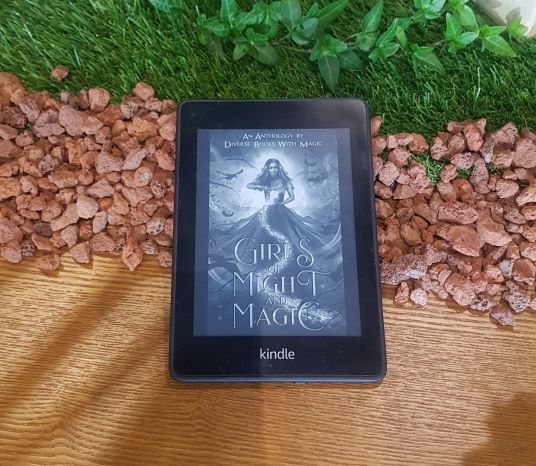 PHOTO ID: Black and white e-cover of Girls of Might and Magic displayed on a black Kindle. The device is on a wooden table, resting on a strip of red volcanic rocks and another strip of grass.