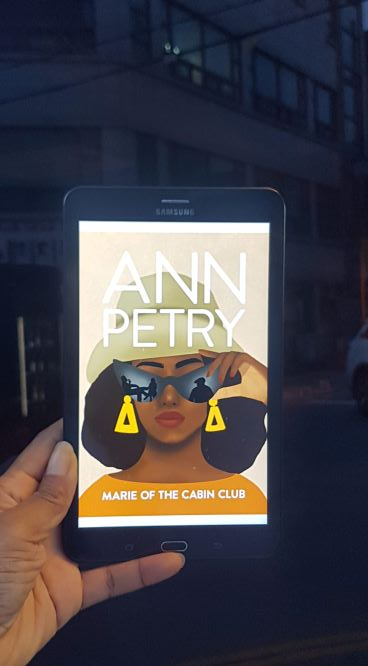 A Black woman's hand holds the colorful cover of Ann Petry's Marie of the Cabin Club in front of a dark city street.