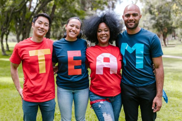 4 smiling people--Asian man, Latina or Indigenous woman, Black woman and Black, mixed or Arab man--stand in a row, wearing colorful shirts that spell out the word TEAM