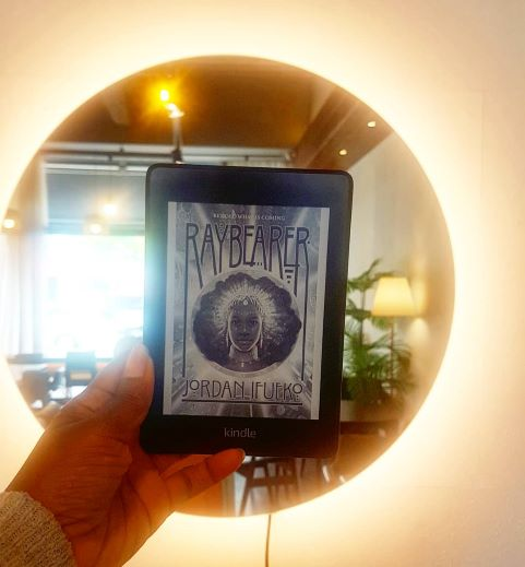 A Black woman's hand holds the brightly lit black and white Kindle cover of Raybearer in front of a round mirror