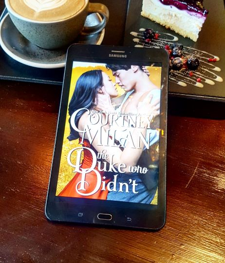 A tablet displays the cover of The Duke Who Didn't, depicting a Chinese couple embracing. They are half-dressed in Victorian clothing. The tablet is on a wooden table with a slice of cheesecake and a latte in the background