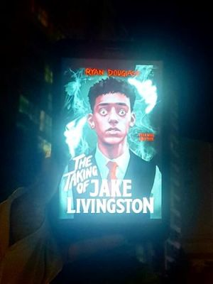 A tablet is held up by a pale, ghostly arm in a dark cityscape. It displays the cover of The Taking Of Jake Livingston, which shows a terrified teenage Black boy in a school uniform staring off into space.