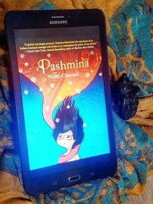 A black tablet displays the cover of Pashmina, which depicts an Indian-American teenage girl wrapped in a red and gold pashmina shawl that floats above her and forms a background for the title of the book. The tablet rests on a blue and gold pashmina, with a tiny black statue of Ganesh peeking over the right side of it.