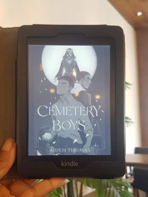 A Black woman's hand(my hand) holds up a black e-reader in front of a leafy green plant inside a sunny cafe. The reader displays the black and white cover of Cemetary Boys, which shows two cartoon-style Latinx teen boys standing back to back with Santa Muerta rising above them in the background.