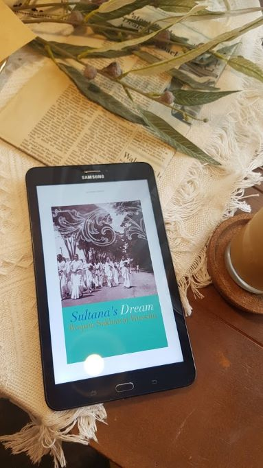 An e-reader lying on a wooden table with a lacy white tablecloth, some green leaves and an iced coffee. The reader shows the cover of Sultana's Dream, which depicts a group of South Asian women walking on a broad country path in a black and white photograph.