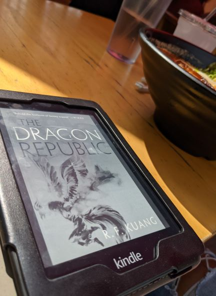 An ebook showing the black and white stylized Chinese culture-influenced cover of The Dragon Republic lays flat on a wooden table. A big black bowl of tan tan mien, or spicy pork and sesame noodles, is in the background.