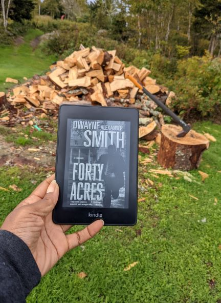A Black woman's hand(my hand) holds a Kindle displaying the black and white cover of Forty Acres in front of a freshly chopped woodpile, complete with axe.