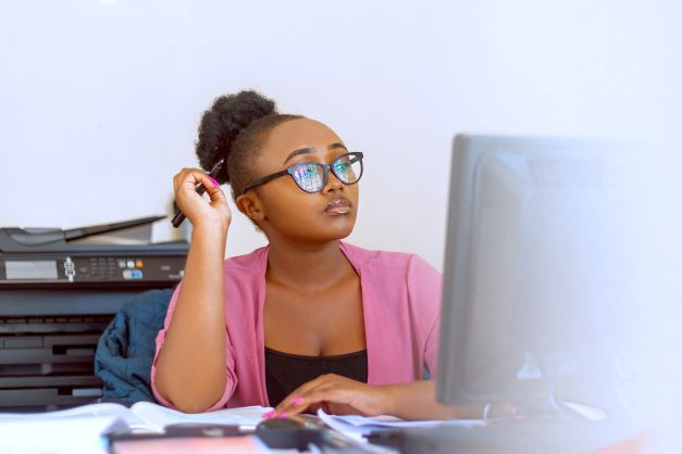 A cute Black woman with glasses, an Afro-puff, wearing a pink cardigan and a black shirt, is sitting in front of a computer monitor deep in thought.