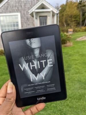 A Black woman's hand holds the ebook of White Ivy up in front of a little island cottage in New England. The cover depicts an Asian woman with her arms wrapped around herself on a black background. The top half of her face is not in the picture.